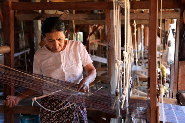 A woman weaving silk fabrics using a hand loom.