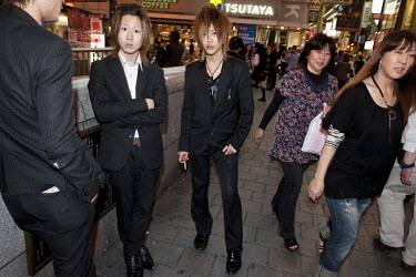 Youths dressed in suits with trendy haircuts, trying to recruit female clients for a host bar in the Dotombori entertainment and shopping district.