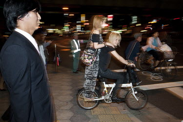 A trendy young couple ride on a bicycle across a road in the Dotombori area.