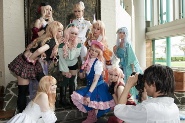 A man photographs a group of Japanese women dressed in cosplay outfits at an event.