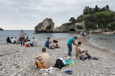 Philippine masseuses at work on the beach of Taormina, which has been a popular tourist destination since the 19th century.