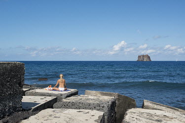 A blonde haired woman meditating on a breakwater, looking towrds the little isle of Strombolicchio in the background. Strombolicchio is a sea stack of volcanic origin two km to the northeast of the is...