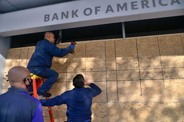 Labourers boards up the windows of a branch of the Bank of America at Connecticut Avenue and Van Ness Street. Nervous shop and business owners boarding up their stores worried about possible violence...