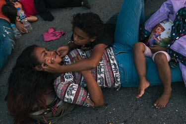 A child plays with its mother as they rest by the side of a highway on the outskirts of Pijijiapan. They are part of a group of migrants from central America making their way north hoping to get to th...