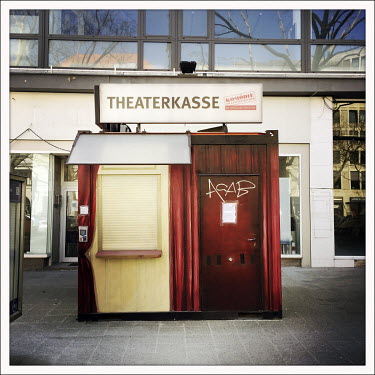 A closed and shuttered theatre ticket kiosk on the Kurfuerstendamm.  The Berliner Ku'damm is lined with luxury boutiques, hotels and restaurants. The coronavirus has resulted in deserted pavements and...