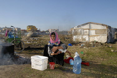 A gypsy woman washes her child outside her shack in an encampment on rubbish strewn waste ground on the outskirts of Tirana.