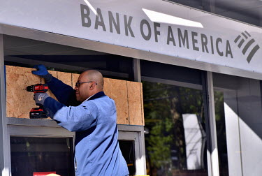 A labourer boards up the windows of a branch of the Bank of America at Connecticut Avenue and Van Ness Street. Nervous shop and business owners boarding up their stores worried about possible violence...