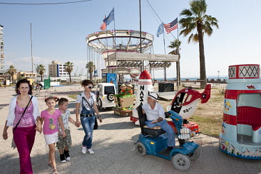 An amputee in a wheelchair begs for money from a pair of women and children walking along the Adriatic coast in the Albanian port city of Durres.