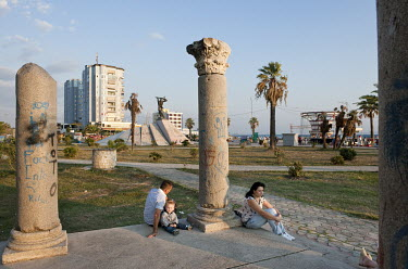 A couple and their child sit among the graffiti covered Roman pillars on the city's Adriatic coast.