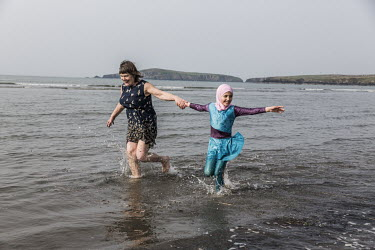 Vicky Moller and Sara Alchik (9) playing together in the sea.   The Alchik family, originally from Syria, have been supported in their resettlement by the UK Community Sponsorship scheme which helps r...