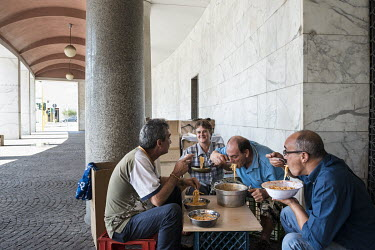 A group of homeless people eating spaghetti in a covered gallery in EUR, a residential and business district in Rome. This area was originally chosen in 1930s as the site for the 1942 world's fair whi...