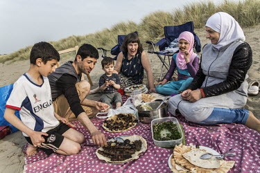 Vicky Moller (centre) eats a picnic at the beach with the Alchik family, Muhaned and his wife Naheda, and children Shadi (8), Sara (9) and Hadi (1).   The Alchik family, originally from Syria, have be...