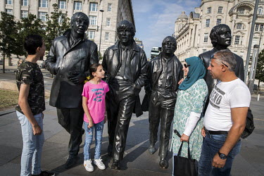 The Khaled Jhayem family (L-R) Adel (14), Ola (11) Ghofran and Ismael stand beside statues of the Beatles on the city's waterfront.  The couple fled Syria in April 2013 with their two children. They s...