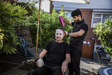 Lufty Al-Shaabin cuts Tim Finch's hair at the Al-Shaabin home in south London. Lufty was a barber in Jordan where his family lived as refugees. Tim is a member of Peckham Sponsors Refugees, a group of...