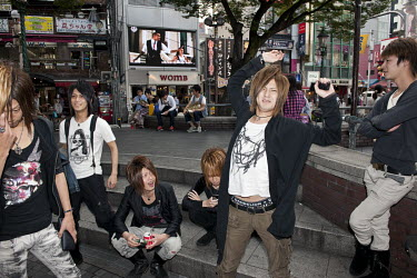 A group of young men with trendy haircuts in Amerikamura or American Village, a sizable retail and entertainment area near Shinsaibashi in the Minami district of Osaka.