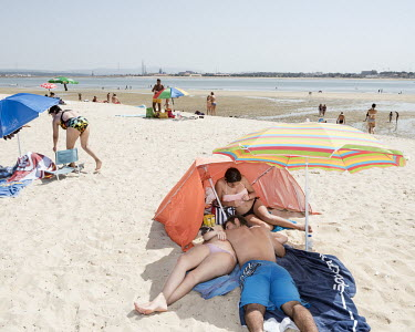 People relax on the beach in Barreiro, once an industrial town that was the home of Companhia Uniao Fabril (CUF) which, from the 1930s until 1974, was one of Portugal's biggest chemical corporations a...