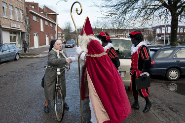 A Catholic nun greets a man dressed as Saint Nicholas or Sinterklaas (Santa Claus) who is out delivering presents to children accompanied by two Swartz Piet blackface characters.