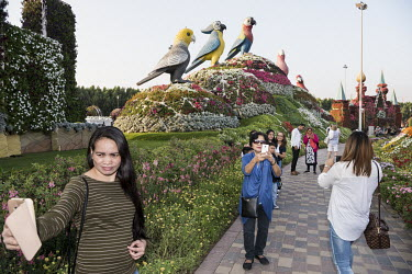 A woman takes a selfie at the Dubai Miracle Garden, a flower garden located in the district of Dubailand.