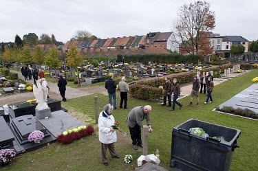 People putting flowers on the graves of their relatives on All Saint's Day.