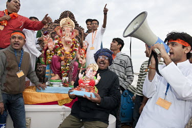 Members of the Indian Hindu community celebrating Ganesh Chaturthi prepare to throw a plaster statue of Ganesha into the Schelde River following a procession to the water's edge.