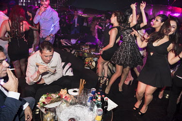 A man eats sushi while beside him a group of women dance in a nightclub on New Year's Eve.