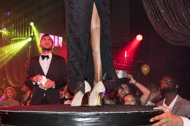 People look up at a woman standing on a podium in a nightclub on New Year's Eve.