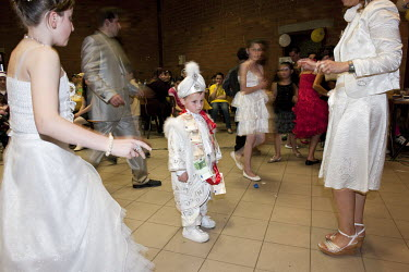 A boy of Turkish descent stands still as his family dance around him in the hall where family and friends have gathered to celebrate his circumcision.