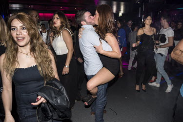 A couple kissing on a nightclub dance floor.