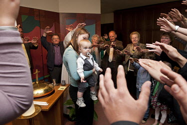 Family members hold up their hands to symbolise protection of the child during a Catholic baptism in a church.