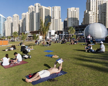 People relax on a lawn at The Beach, a promenade with restaurants and attractions on the Persian Gulf shoreline.