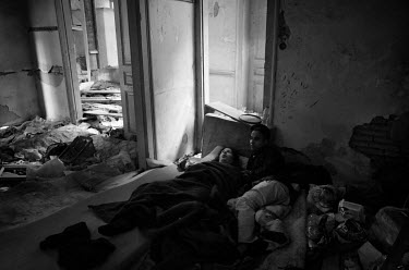 A Bangladeshi man and a disabled woman lie on an old matress inside an abandoned building.