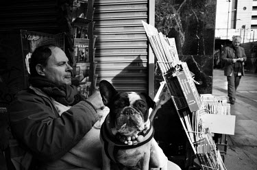A vendor at a news stand sitting with his dog outside his kiosk.