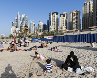 A veiled woman sits on the sand at the Beach near the Dubai Marina.