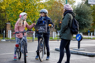 A woman and a child riding bicycles stop to talk to a pedestrian in Dulwich.