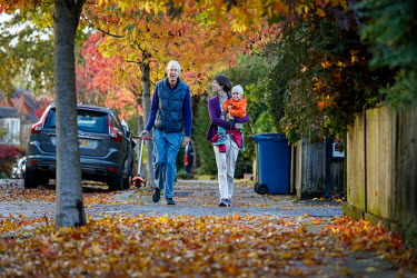 An elderly couple walks with a child on a road closed to motorised traffic in Dulwich.
