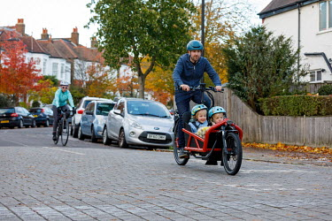 A man rides a bicycle, adapted with a children's compartment, along a residential road in Dulwich.