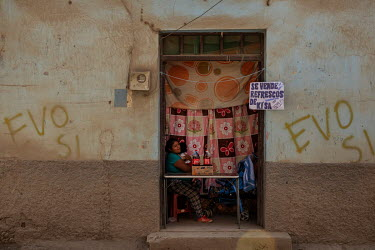 A woman sells coca-cola at the door of her house which is covered by graffiti in support of the former president of Evo Morales, in Chulumani, traditionally a coca producing area.