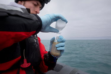 Scientist Nacim�Guellati collects water samples for eDNA sampling from the waters around Elephant Island. �  Environmental DNA monitoring uses filters to trap free-floating DNA that has been left...