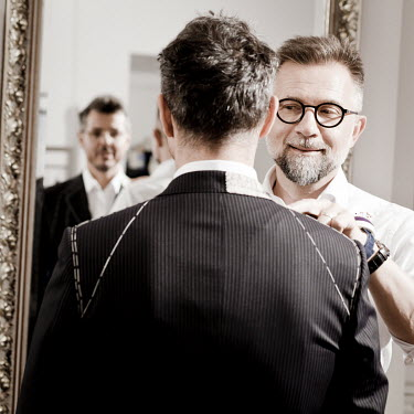 Artisan tailor Janusz Bielenia measures a client for a suit at his workshop.