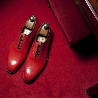 A pair of red shoes made by the artisan shoemaker Jan Kielman in his workshop.