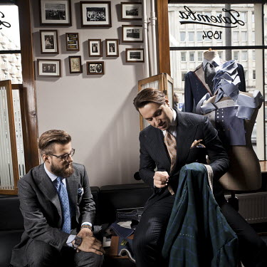Artisan tailor Maciej Zaremba at his workshop with a client.