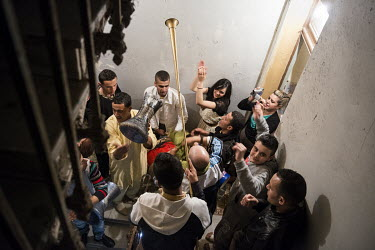 A band playing traditional instruments plays outside a flat in the stairway of an apartment block during celebrations for a marriage.