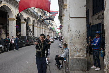 A youth waves a crutch while socialising with friends on an arcaded shopping street in the the lower casbah.