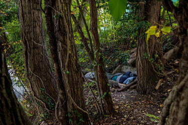 A homeless Nigerian man sleeps on concrete culvert, the only flat spot on the steep banks of the Avre River, behind the Queue d'Avre sport complex. The trees and undergrowth growing on the bank mean t...