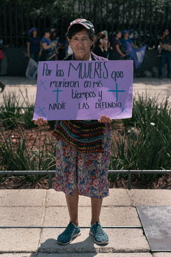 Josefina Rodriguez (80) holds a sign beside the Monument to the Revolution before a protest on Women's Day. ''I feel happy and sad to be here because there are many people who are very sore from losin...