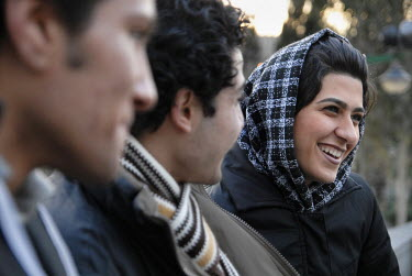 Male and female students socialise in a park. According to religious regulations in Iran, both sexes have to keep separate in public life, and women have to cover their hair completely.