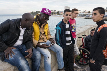 A group of youths socialise on the Mediterranean seafront.