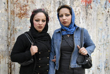 Two young women wearing make-up and revealing their dyed hair, going against religious guidelines which state that women should not reveal any of their hair.