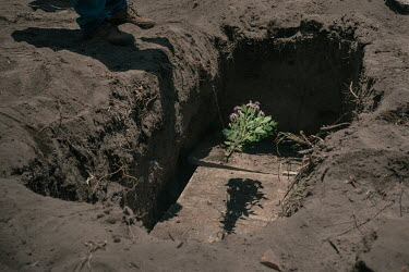 A man throws a bouquet of flowers into the grave before a worker fills it at the COVID-19 section of the San Lorenzo Tezonco public cemetery in Iztapalapa.