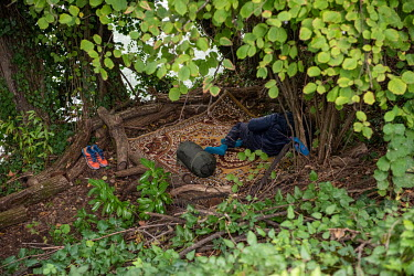 A homeless Nigerian man rests on a rug among the trees and undergrowth growing on the banks of the Avre River, behind the Queue d'Avre sport complex. The trees and the steepness of the bank mean that...